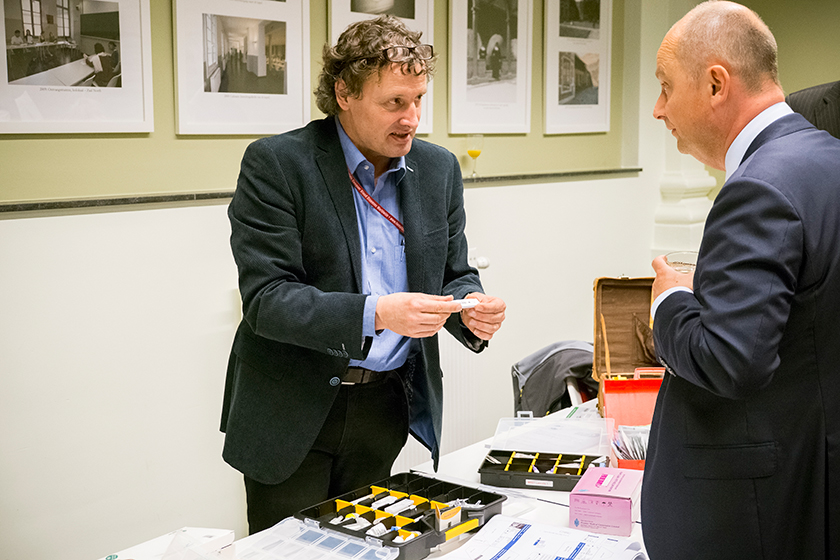 Prof. Jan Jacobs (left) explains malaria rapid tests to one of the guests.